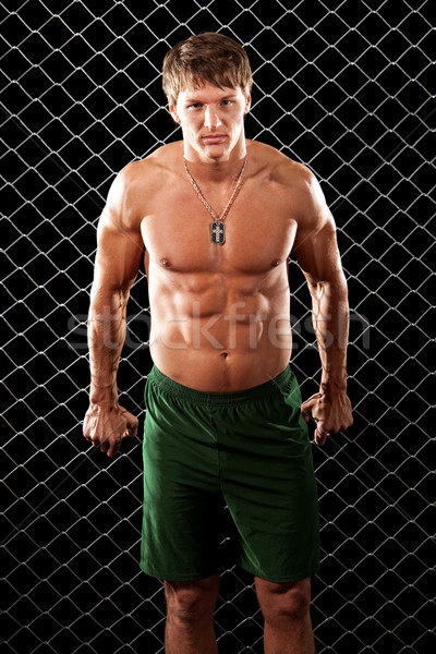 Male bodybuilder posing in front of chain link. Stock photo © nickp37