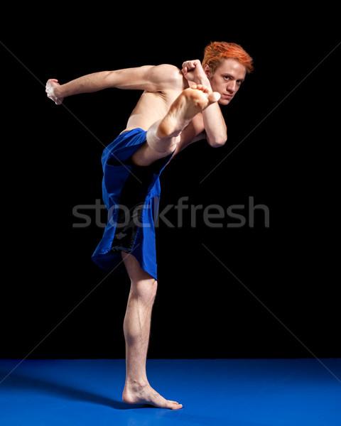 Martial artist in blue shorts. Studio shot over black. Stock photo © nickp37