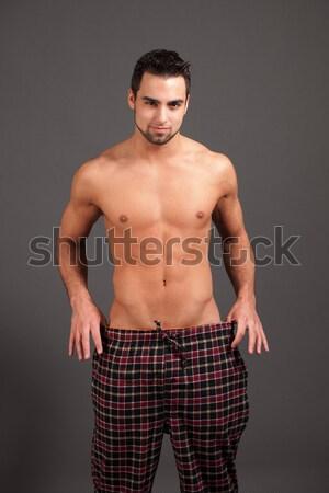 Stock photo: Attractive man in pajamas. Studio shot over grey.