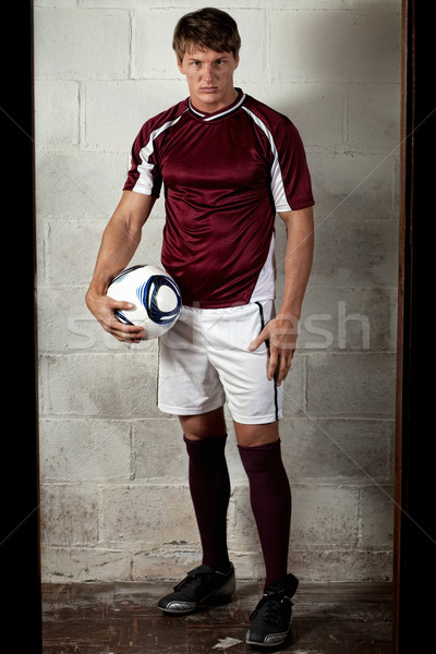 Male soccer player in front of concrete block wall. Stock photo © nickp37