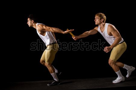 Relay racers passing the baton. Studio shot over black. Stock photo © nickp37