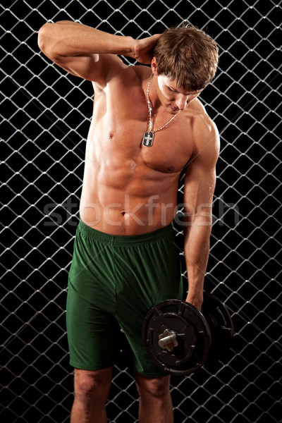 Man lifting weights in front of chain link. Stock photo © nickp37