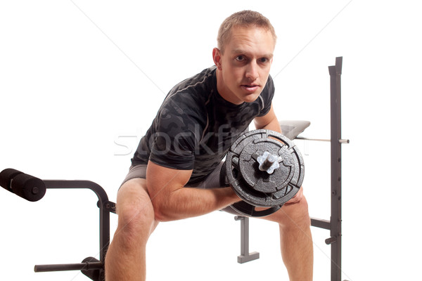 Young man lifting weights. Studio shot over white. Stock photo © nickp37