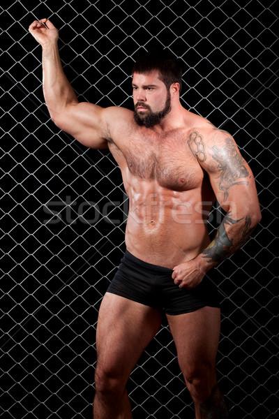 Bodybuilder posing in front of chain link. Stock photo © nickp37
