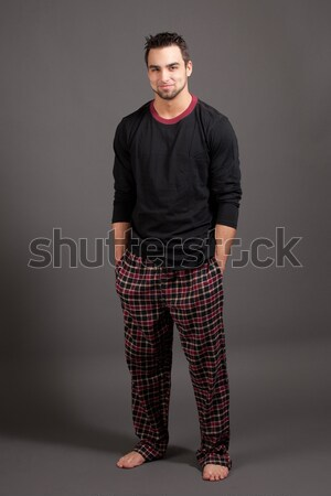 Stock photo: Attractive man in pajamas. Studio shot over grey.