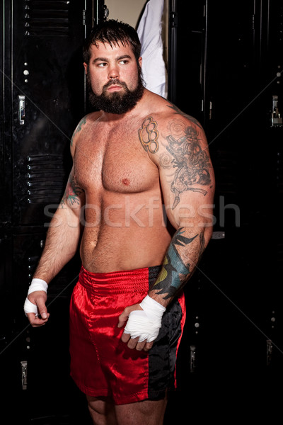 Muscular fighter in a locker room before or after a match. Stock photo © nickp37