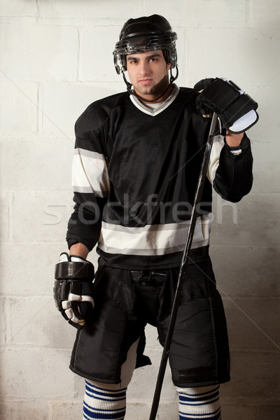 Ice hockey player in front of concrete block wall. Stock photo © nickp37
