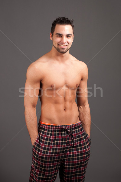 Attractive man in pajamas. Studio shot over grey. Stock photo © nickp37