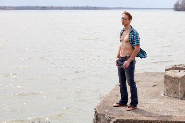 Young man at the edge of a body of water. Standing in the wind. Stock photo © nickp37