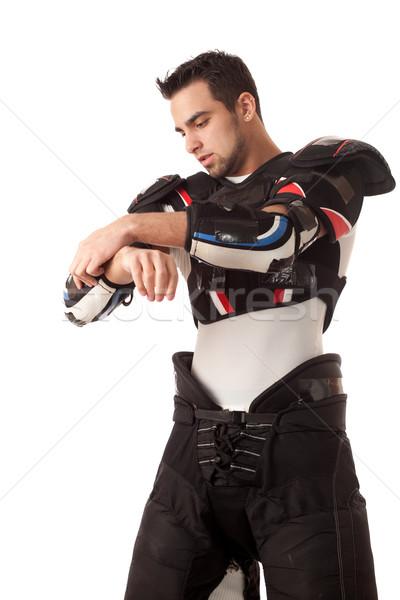 Ice hockey player dressing. Studio shot over white. Stock photo © nickp37