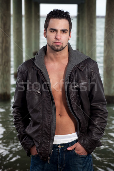 Man in jeans and leather jacket beneath a pier. Stock photo © nickp37