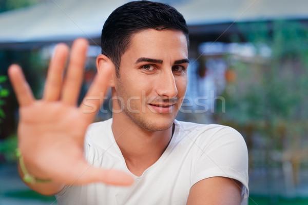 Fiatalember emelkedő kéz készít stop kézmozdulat Stock fotó © NicoletaIonescu