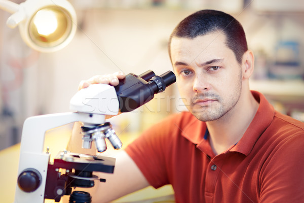 Skeptical Young Male Researcher with microscope Stock photo © NicoletaIonescu