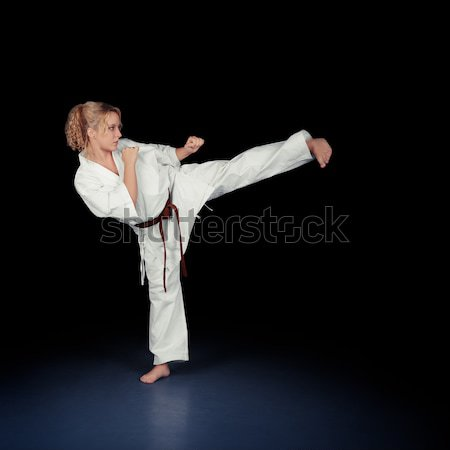 Young Karate Woman in a White Kimono Kicking Stock photo © NicoletaIonescu