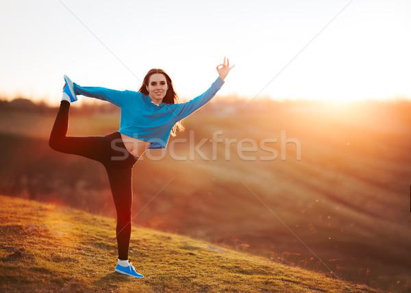 Boldog fitt nő nyújtás természet naplemente Stock fotó © NicoletaIonescu