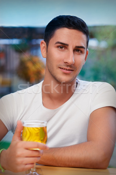 Young Man Holding a Glass in a Bar Stock photo © NicoletaIonescu