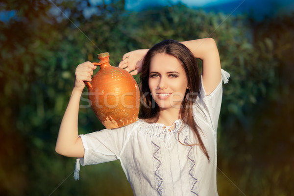 Young Woman with Clay Pitcher  Stock photo © NicoletaIonescu