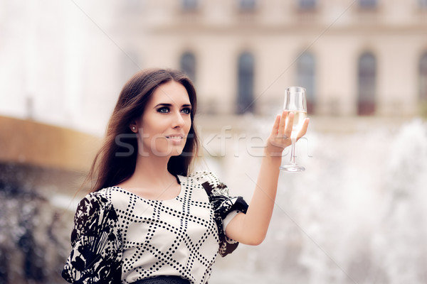 Beautiful Girl with Champagne Glass Celebrating by the Fountain Stock photo © NicoletaIonescu