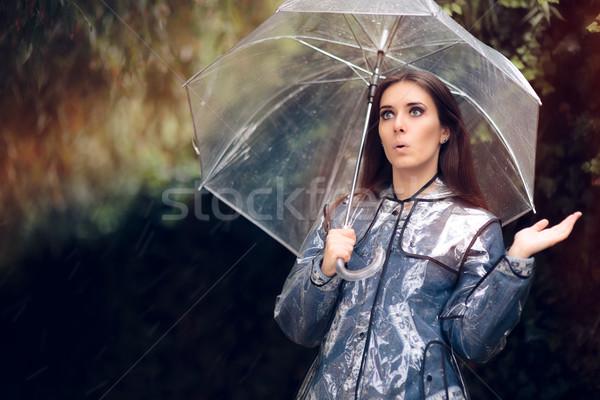Meglepődött nő esőkabát átlátszó esernyő lány Stock fotó © NicoletaIonescu