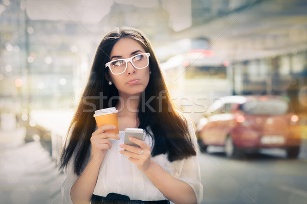 Disappointed Young Woman Holding Smartphone and Coffee Cup Stock photo © NicoletaIonescu