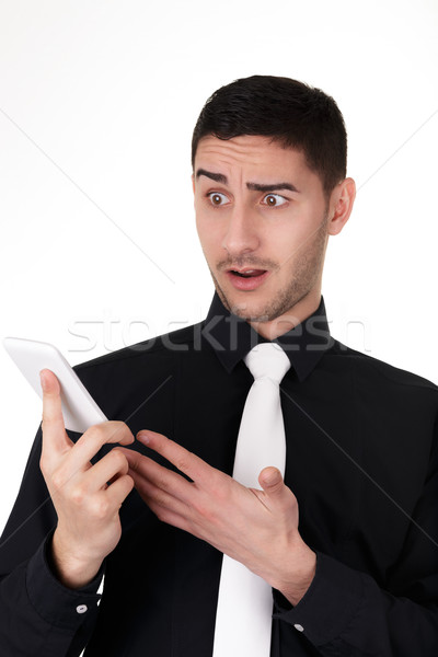 Young Businessman Looking Surprised at His Smart Phone  Stock photo © NicoletaIonescu
