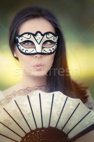 Surprised Young Woman with Mask and Fan Stock photo © NicoletaIonescu