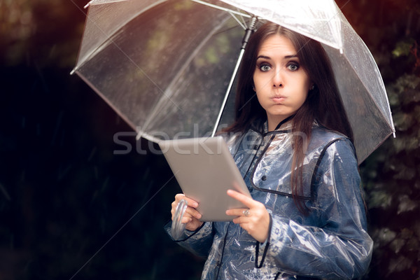 Funny Woman with Raincoat and Umbrella Holding Pc tablet Stock photo © NicoletaIonescu