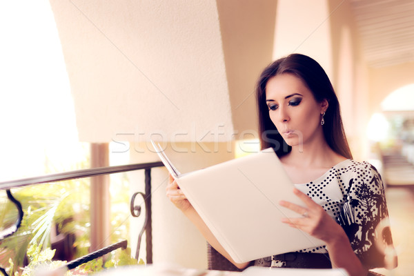 Surprised  Woman Choosing from Restaurant Menu Stock photo © NicoletaIonescu
