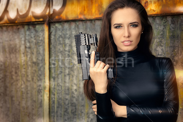 Spy Agent Woman in Black Leather Suit Holding Gun Stock photo © NicoletaIonescu