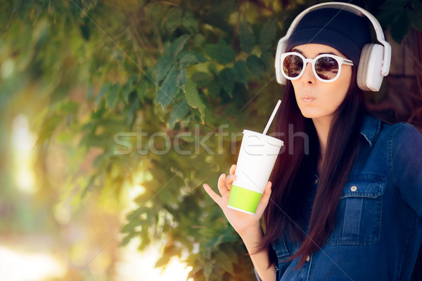 Funny Girl in Jeans Outfit Wearing Sunglasses Drinking Juice and Listening to Music Stock photo © NicoletaIonescu