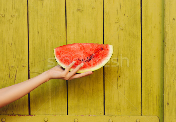 Hand Holding Watermelon Slice on Green Wooden Background Stock photo © NicoletaIonescu