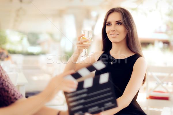 Happy Actress Holding a Glass in Movie Scene Stock photo © NicoletaIonescu