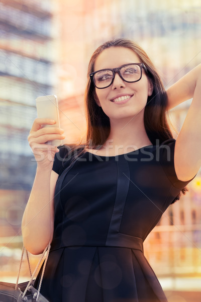 Stock photo: Young Woman with Shopping Bag and Phone Out in the City