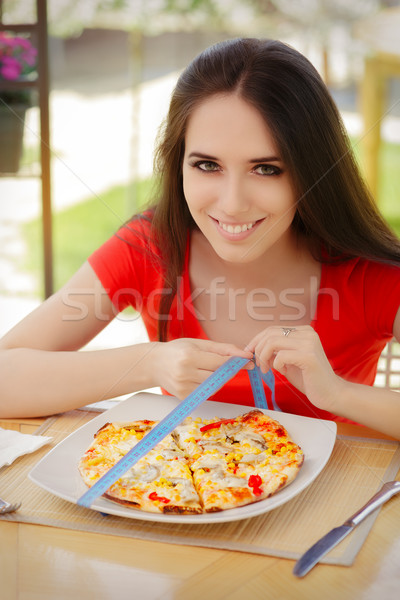 Young Woman Checks on Pizza Size with Measuring Tape  Stock photo © NicoletaIonescu