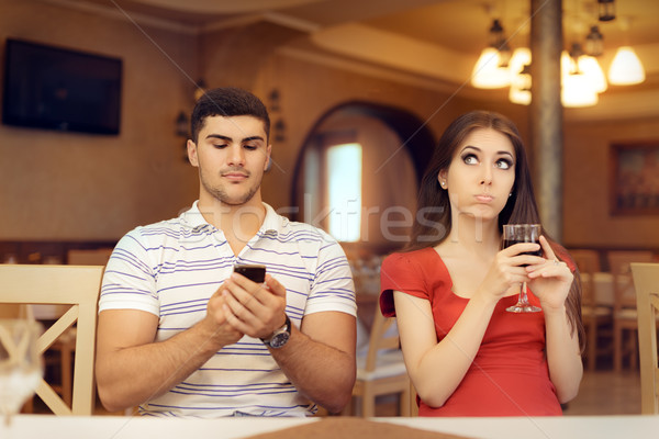 Bored Girl in a Date with Her Boyfriend Addicted to his Smartphone Stock photo © NicoletaIonescu