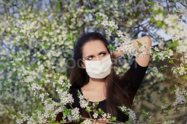 Woman with Allergy with Respirator Mask in Spring Blooming Decor Stock photo © NicoletaIonescu