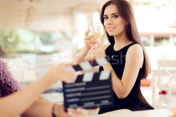 Stock photo: Happy Actress Holding a Glass in Movie Scene
