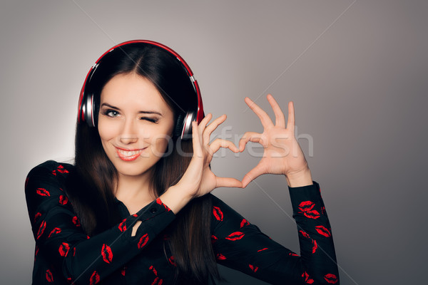 Smiling Girl with Headphones Making Heart Sign Stock photo © NicoletaIonescu