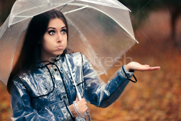 Woman with Transparent Raincoat and Umbrella Checking for Rain Stock photo © NicoletaIonescu