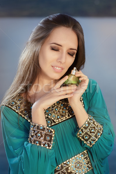 Young Woman Holding Perfume Bottle in Seaside Landscape Stock photo © NicoletaIonescu