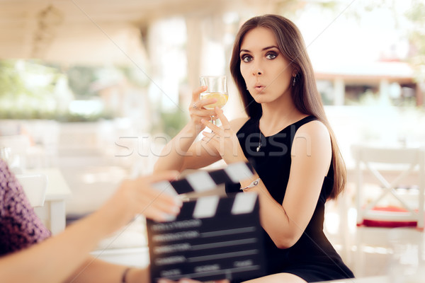 Surprised Actress Holding a Glass in Movie Scene Stock photo © NicoletaIonescu