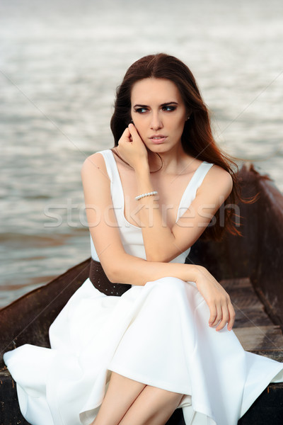 Stock photo: Sad Woman in White Dress Sitting in an Old Boat
