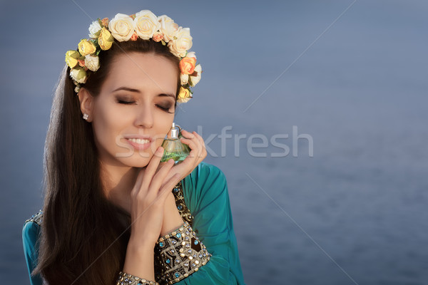Young Woman With Floral Wreath Holding Perfume Bottle in Seaside Landscape Stock photo © NicoletaIonescu