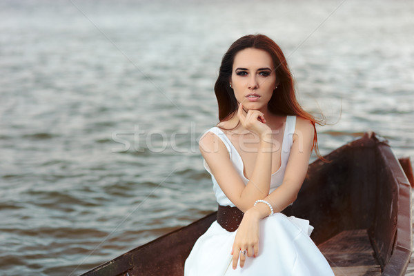 Thoughtful Woman in White Dress Sitting in an Old Boat  Stock photo © NicoletaIonescu