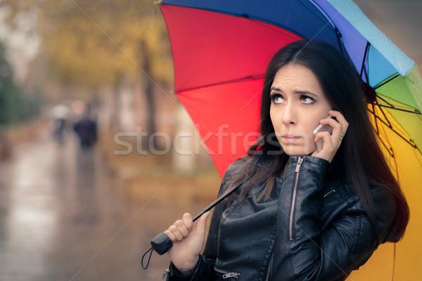 Autumn Girl Holding a Rainbow Umbrella and a Smartphone Stock photo © NicoletaIonescu