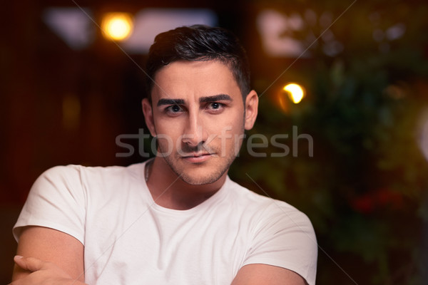 Surprised Young Man Sitting in a Restaurant Stock photo © NicoletaIonescu