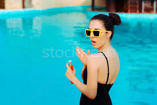 Summer Girl Applying Suncream Lotion by the Pool Stock photo © NicoletaIonescu