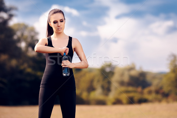 Fitness Girl with Water Bottle Hydrating after Outdoor Workout Stock photo © NicoletaIonescu