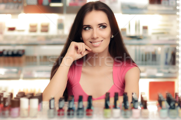 Happy Girl Choosing Between Bottles of Nail Polish Stock photo © NicoletaIonescu