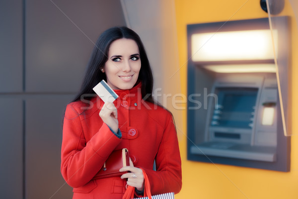 Happy Shopping Woman Holding Credit Card in front of an ATM Stock photo © NicoletaIonescu
